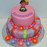 Dora The Explorer Cake Chocolate cake filled with chocolate buttercream. Flowers are fondant and Dora is actually a candle. Thanks for looking! :)