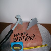 Carpenter's Tools Cake This is a small yellow cake with fondant to make the cake look like a wood block. The tools are made from fondant.