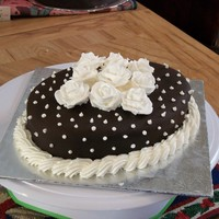 Chocolate With Polka Dots. Chocolate cake covered in chocolate fondant. BC piping and dots. Royal icing flowers.