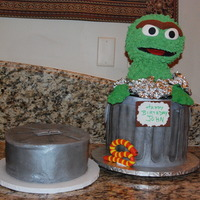 "Oscar The Grouch Trash can is a 10"" cake dummy and a 10"" vanilla cake filled with choc fudge bc. Oscar is make of RKT and iced in RI."