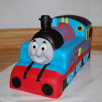 3D Sculpted Thomas The Tank Engine 1/2 vanilla, 1/2 chocolate cake, vanilla buttercream frosting & covered in buttercream fondant. All decorations are fondant.