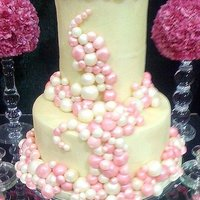 Tiny Bubbles Two tiered wedding cake wrapped in fondant accented by pink and creme sugar balls