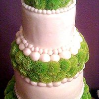 Going Green Two tiered wedding cake wrapped in fondant and accented by fresh green button flowerss