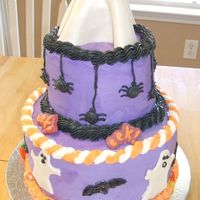 Halloween Cake With Ghosts & Spiders Cake is frosted in buttercream. Ghost around side and on top are fondant. Eek signs are candymelts. Spiders are buttercream. Cake made for...