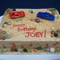 "Cars Cake My son is obsessed with ""Cars."" Marble cake with peanut butter buttercream frosting. I used crushed graham crackers to make the..."