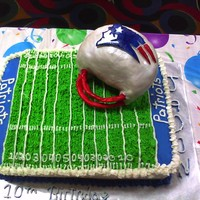 Football Cake Half chocolate half white cake, w/ buttercream icing. Football helment made out of RKT's covered w/ MMF and hand painted.