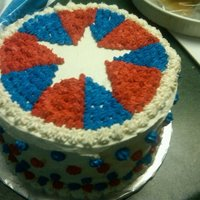 4Th Of July Star Covered cake with white buttercream and filled in wedges with red/blue star tip, leaving white star shape in center.