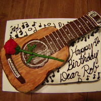Rob's Guitar Hand carved guitar on top of layered cake. Buttercream rose