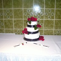 Black, Red And White   This is a three layer stacked round buttercream iced wedding cake with black ribbon and red roses.