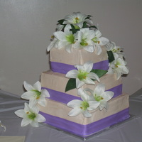 Ivory And Lillies This is an ivory three layer stacked buttercream cake with wisteria colored ribbon and white lillies.