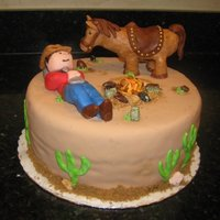 Cowboy And Horse Cowboy and horse cake with fondant decorations.