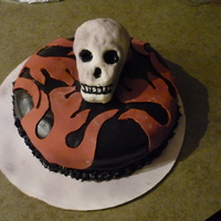 Death Race.....first Time Skull  This was a very fun project. The skull was my very first attempt using rice krispies and fondant. The cake is almond vanilla with orange...