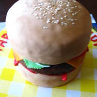 Burger Cake  Made with layers of vanilla cake, red velvet, and chocolate cake.With vanilla buttercream, chocolate buttercream, and chocolate ganache/...