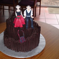 A Red And Black Brides Dress  This cake is a 3 tied wedding cake with chocolate cigrellos and is a topsy turvy cake.The bride and groom are made entirely of modelling...