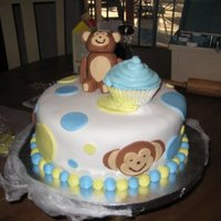 Monkey B-Day Cake 2-tier, 9 inch chocolate cake with cherry filling. All the decorations are made of fondant. The monkey is a fondant-gum paste mix. I was...