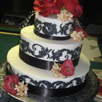 Damask Wedding Cake 3 tier white wedding cake with damask print on each tier accented with red roses and white accent flowerswww.sugarnspicepatisserie.com