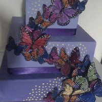 Butterfly Cake 3 tier purple butterfly cake with multi color monarchs cascading up it with yellow dot accents. www.sugarnspicepatisserie.com