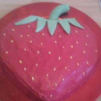 Strawberry Cake Heart shaped cake with red marshmellow fondant, and green trim and yellow seeds.