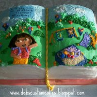 Dora Storybook Cake Hand carved open book cake, decorated primarily in buttercream with a few fondant accents.