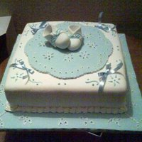 Baby Shower Cake Coconut cake with white and blue fondant.Bootees are gumpaste, Ribbons are satin.