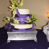 Purple Plum Wedding Cake Purple and white weddding cake with fresh Lilies. Fondant swags.