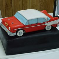 57 Chevy Bel Air 4Door cake shaped like 57 chevy bel air - covered in fondat ; sitting on top of another cake
