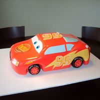 Lightning Mcqueen Car cake shaped into lightning mcqueen car - covered in fondant