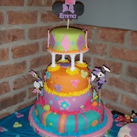 Club House Minnie Mouse This is a four tier chocolate with raspberry cake covered with MMF. The decorations are MMF too.