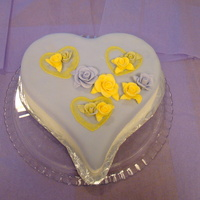 Hearts And Roses Heart cake covered in white fondant with a purple fondant overlay. Three embrodery heart with rosesbuds. Medium roses in center with...
