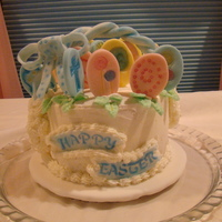 "Happy Easter  6"" x 4"" w/BC icing. Fondant for decorations. Stamps and pearl dust used to accent eggs. The bow was imprinted with star end of..."