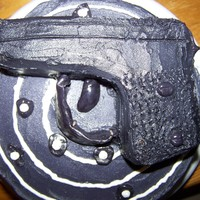 9Mm Cake for a friends dad that loves guns.... 9mm is made of cake sitting on top of a target that is two layer vanilla cake. buttercream icing and...