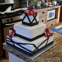 "Black And White Wedding Cake With Red Vanda Orchids  This was a wedding cake done for my cousin's wedding in November. The orchids are made of gum paste. The black ""ribbon""..."