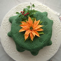 Tablecloth Christmas Cake Rich fruit cake covered with marzipan and a 'tablecloth' of sugarpaste.Poinsettia, holly and ivy made with flowerpaste.