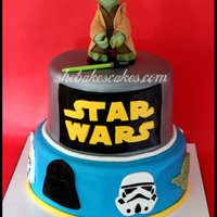Star Wars Cake  2 tier Star Wars themed cake. 3D sculpted Yoda on top! Various faces/masks surround the bottom tier including Darth Vader, Clone Tooper,...
