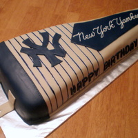 Ny Yankees Pennant   Chocolate cake with MMF over chocolate buttercream. NY is MMF, stripes are hand painted and lettering is piped buttercream.