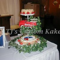 Fireman/groom 3 Tier Floating stand. Top, 6 Cheesecake, Kiwi & StrawberriesBottom 10 Cheesecake, Colorflow Emblem from Fire Helment. Characterture...