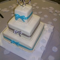 Winter Wonderland Three tier buttercream wedding cake with accents of blue and silver ribbon.