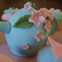Teapot Cake And Cupcakes  Mini Teapot cake with matching cupcakes. Vanilla cake covered in White chocolote and fondant. All flowers, leaves and butterflies are made...