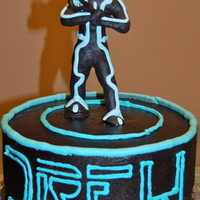 Tron Legacy Tron Legacy cake for a boy who also plays lacross. He's holding a lacross stick.