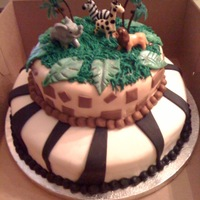 In The Jungle Two tiered chocolate cake with strawberry filling, covered with buttercream and vanilla fondant. The animals are plastic, and the leaves...