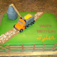 Semi-Truck And Grain Bin Birthday Cake 11x15 chocolate cake, done in buttercream. The truck and grain bin are done with rkt, and covered in fondant