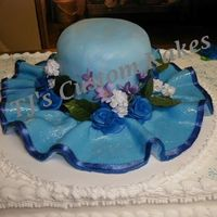 Martha's Hat Full Sheet Main Cake W/W, 2/6 for top of hat. Colored Blue Fondant trimmed in thin blue satin ribbon w/ blue flowers. Top Dusted with Pearl...