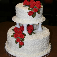 First Wedding Cake   Top layer is a double 6 inch and bottom is a double 10 inch. The roses are made out of royal icing.