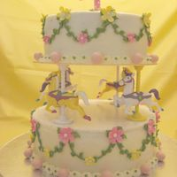 Carousel Cake   Buttercream icing with fondant flowers and number 4. pink candy balls.