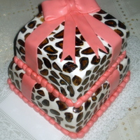 Animal Print Cake Two tier animal print gift box cake. Base is chocolate cake with strawberry icing, and the top is chocolate cake filled with coconut.