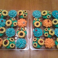 "Flower Cupcakes Sunflowers were from the ""Hello, Cupcake"" book. Other flowers were done with buttercream and a petal tip"