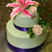 Sarah S 5,8 round. light green BC icing, purple ribbon border, and sugar flowers. the bridal shower was garden party themed. the cake is vegan...