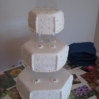October 2, 2010 - Wedding Cake For Jeanie & Mark  Three tier wedding cake for my boss' sister's wedding.MMF over an extra thick layer of buttercream. Piped scroll work, hand...