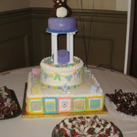 Baby Shower Cake W/ Teddy & Baby Clothes Tier Cake w/ square tier of baby blocks,next tier baby clothes, Purple tier w/teddy bear ,in middle of tiers is an umbrella (purple was the...