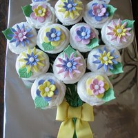 Flower Cupcake Bouquet I first covered the cupcakes with buttercream icing, then added the fondant flowers and leaves. The bow and banner is also made with...